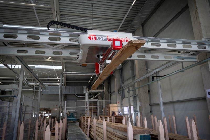 Die neue Anlage beschleunigt das Massivholzhandling bei der Feil GmbH in Siegsdorf. Die Spezialtraverse integriert einen Laserscanner sowie eine Abstreifmechanik. Bild: Barbaric
