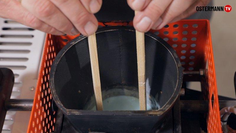 Um das Schmelzkleberbecken am nächsten Morgen ohne großen Aufwand zu reinigen, steckt man mehrere kleine saubere Holzstäbchen in das noch warme Klebstoff-Reiniger-Gemisch. Bild: Ostermann